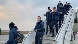 Игроки сборной Казахстана по футболу спускаются по трапу самолета