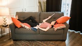 Женщина со щеткой в руках лежит на диване