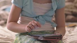 Девочка сидит на кровати с планшетом