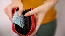 Девушка достает из кошелька помятую банкноту