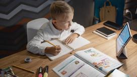 Мальчик делает уроки и смотрит на планшет