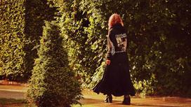 Девушка в длинной черной юбке и куртке идет по саду