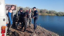 группа мужчин стоит на берегу водоема