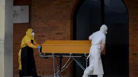 Медработники в защитных костюмах везут гроб