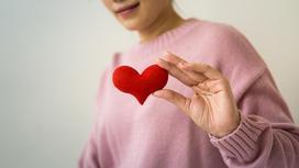 Девушка в розовом свитере с сердечком в руках