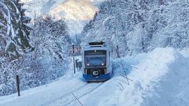 Поезд едет по заснеженным путям