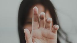 Девушка показывает жест рукой перед лицом