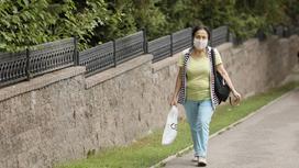 Женщине в маске идет по улице