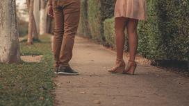 Девушка и парень стоят на тротуаре