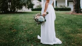 Невеста стоит на газоне в белом платье