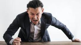 Мужчина в гневе бьет кулаком по столу