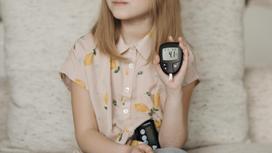 Девочка держит глюкометр