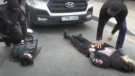 Двое мужчин лежат на земле, их задерживают силовики