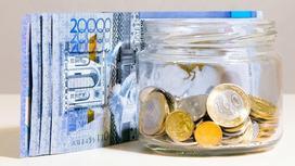 Купюры тенге лежат рядом с банкой монет