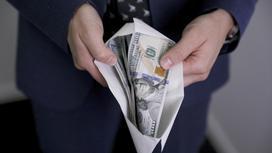 мужчина держит конверт с долларами