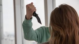 Мужчина замахивается с ножом на женщину