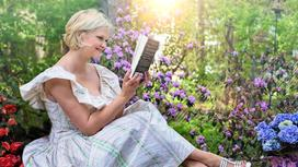 Девушка в саду читает книгу