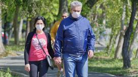 Мужчина и женщина в масках идет по аллее