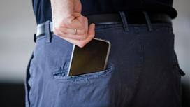 Мужчина достает телефон из заднего кармана брюк