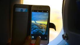 смартфон с видом самолета на экране