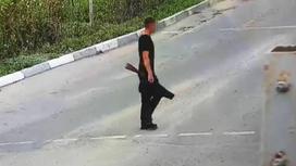 Мужчина с карабином, завернутым в одежду, стоит на улице