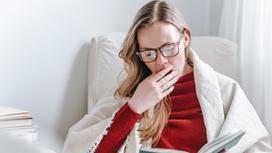 Уставшая девушка в очках читает книгу