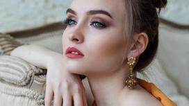 Девушка с красивым вечерним макияжем сидит на диване