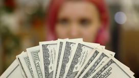 девушка держит доллары веером