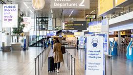 Девушка с чемоданом идет по аэропорту