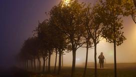 Девушка идет по улице, погруженной в туман