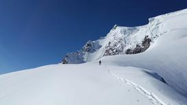 Альпинист взбирается на заснеженную гору