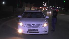 Мужчина стоит у белого авто без номеров