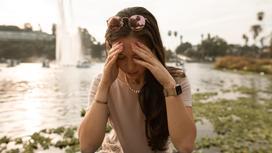 Девушка сидит возле фонтана и держится за голову