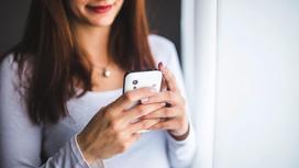 Молодая девушка держит в руках смартфон
