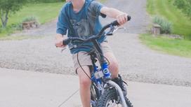 Велосипедте отырған бала