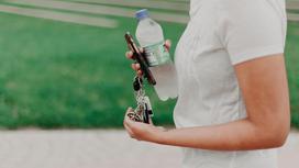 Женщина держит ключи от автомобиля и воду