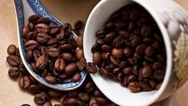 Зерна кофе в перевернутой чашке и керамической ложке