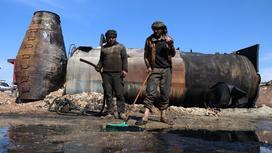 Мужчины убирают обломки ракеты в Алеппо