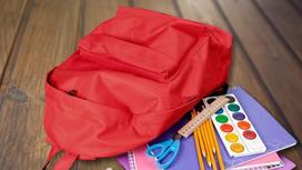 Рюкзак и школьные принадлежности лежат на паркете
