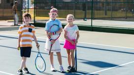 Девочки и мальчик стоят с ракетками для тенниса