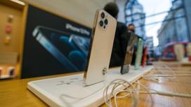 Смартфоны марки iPhone стоят на торговых столах-витринах в магазине