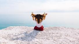 Девушка на берегу держит волосы