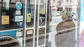 Женщина в маске на остановке около автобуса