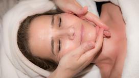Косметолог женщине делает массаж лица