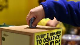 Мужчина кладет деньги в ящик для пожертвований