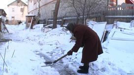 Пожилая женщина убирает снег лопатой