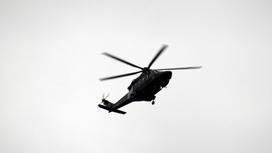 Черный вертолет на фоне пасмурного неба