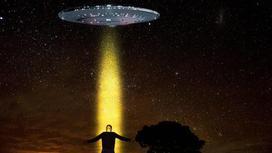 Касмоческий корабль на фоне звездного неба, на переднем плане человек. На него направлен свет из корабля