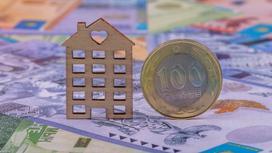 Монета тенге стоит ребром рядом с деревянной формой дома