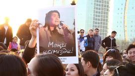 Плакат с Батырханом Шукеновым держат в руках